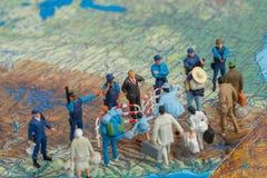 Миниатюрные пограничные патрули США концепции людей игрушки против группы в составе переселенец Стоковые Изображения