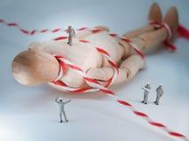 Миниатюрные помогли работники, который двигают гигантскую деревянную куклу Стоковые Изображения RF