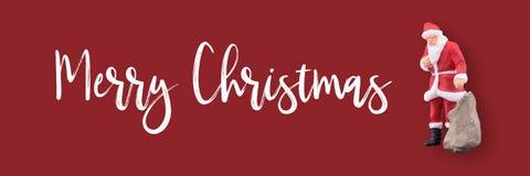 Миниатюрные Санта Клаус и подарки кладут в мешки с текстом веселого рождества с космосом экземпляра стоковое фото rf