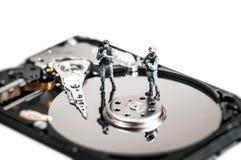 Миниатюрные солдаты защищая жесткий диск компьютера изолированная принципиальной схемой белизна технологии Стоковые Изображения