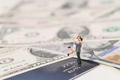 Миниатюрные счастливые пары держа один другого стоя на кредитной карточке и куче счетов доллара США, финансовом менеджменте семьи стоковые изображения