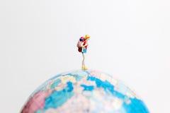 Миниатюрные люди вычисляют положение на карте мира глобуса Стоковое Изображение RF