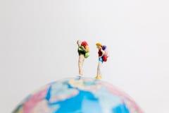 Миниатюрные люди вычисляют положение на карте мира глобуса Стоковое Фото