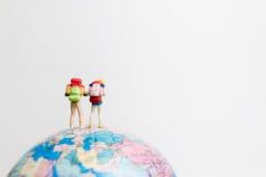 Миниатюрные люди вычисляют положение на карте мира глобуса Стоковые Фото