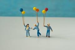 Миниатюрные люди при семья держа воздушный шар с голубым bac цвета Стоковые Фотографии RF