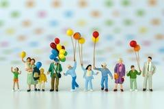 Миниатюрные люди при семья держа воздушный шар с точкой цвета шипучки Стоковые Фото