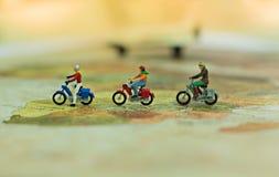 Миниатюрные люди, путешественники с велосипедом на карте мира, cyling к назначению Стоковая Фотография RF