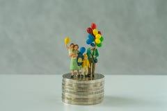 Миниатюрные люди, семья держа воздушный шар стоя на стоге монеток как финансовое дело или счастливая концепция выхода на пенсию стоковое изображение
