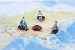 Миниатюрные люди сидят на карте мира international дела Стоковая Фотография RF