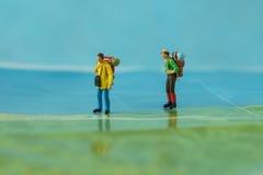 Миниатюрные backpackers идя на карту как concep перемещения предпосылки Стоковое фото RF