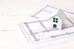 Миниатюрный белый дом игрушки с чертежом плана дома на белом woode Стоковая Фотография RF