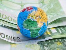 Миниатюрный глобус на предпосылке банкнот евро в дневном свете Стоковые Изображения RF