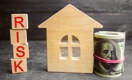 """Миниатюрный деревянный дом, доллары и надпись """"риск """" Покупка дома, квартиры и финансовых рисков Утрата имущества для стоковое фото rf"""