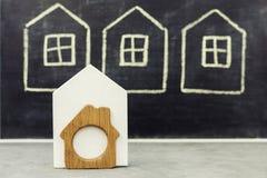 Миниатюрный деревянный дом на вычерченной предпосылке домов Стоковые Изображения