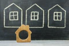 Миниатюрный деревянный дом на вычерченной предпосылке домов Стоковые Фото