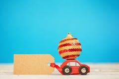Миниатюрный красный автомобиль нося подарочную коробку рождества на голубой предпосылке Новый Год принципиальной схемы рождества стоковые изображения