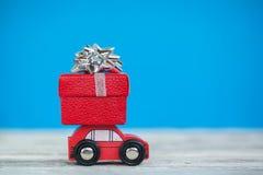 Миниатюрный красный автомобиль нося подарочную коробку рождества на голубой предпосылке Новый Год принципиальной схемы рождества стоковое изображение rf