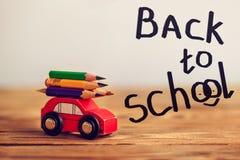 Миниатюрный красный носить автомобиля красочные карандаши на деревянном столе задняя школа принципиальной схемы к стоковое изображение
