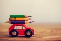 Миниатюрный красный носить автомобиля красочные карандаши на деревянном столе задняя школа принципиальной схемы к стоковая фотография rf