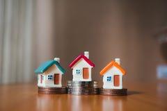 Миниатюрный красочный дом на монетках стога стоковое фото rf
