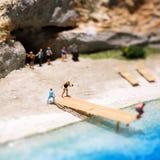 Миниатюрный мир: люди в различных ситуациях принимая праздник на пляж Образ жизни лета, каникулы и концепция туризма Стоковая Фотография RF