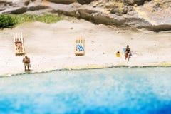 Миниатюрный мир: люди в различных ситуациях принимая праздник на пляж Образ жизни лета, каникулы и концепция туризма Стоковая Фотография