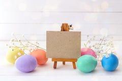Миниатюрный мольберт с пасхальными яйцами и белыми цветками на задней части белизны Стоковые Фотографии RF