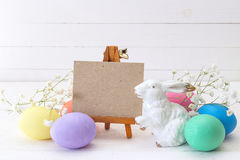 Миниатюрный мольберт с пасхальными яйцами и белым кроликом на белом backg Стоковое Изображение