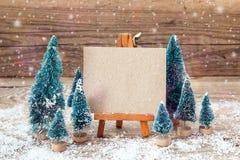 Миниатюрный мольберт с пустой карточкой и миниатюрные ели дополнительный праздник формата карты стоковые изображения