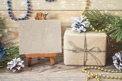 Миниатюрный мольберт с пустой карточкой, подарочной коробкой, ветвями сосны и Chr стоковая фотография rf