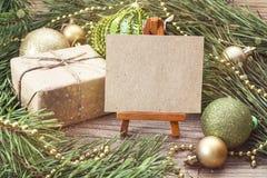 Миниатюрный мольберт с пустой карточкой, подарочной коробкой, ветвями сосны и Chr Стоковое фото RF