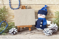 Миниатюрный мольберт с пустой карточкой, снеговиком игрушки, ветвями сосны и стоковое изображение