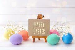 Миниатюрный мольберт с сообщением счастливой пасхой, яичками и цветками на w стоковая фотография rf