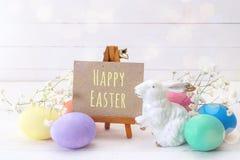 Миниатюрный мольберт с сообщением счастливые пасхальные яйца пасхи, и белизна стоковое изображение rf