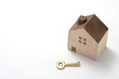 Миниатюрный дом и ключ изолированные на белой предпосылке Стоковые Изображения