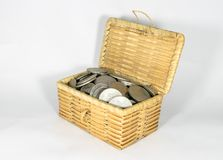 Миниатюрный плетеный комод заполнил с различными монетками на белой предпосылке, сохраняя концепцию денег Стоковые Фотографии RF