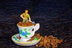 Миниатюрный работник копая зерна кофе от чашки чая Стоковые Изображения