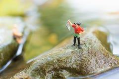 Миниатюрный рыболов сидя на камне, удя в реке Фото взгляда макроса, польза как концепция карьеры рыбной ловли Стоковая Фотография