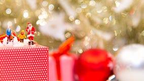 Миниатюрный Санта Клаус стоя с большими присутствующими коробками как с Рождеством Христовым стоковое фото