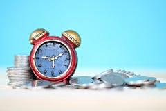 Миниатюрный стог часов и монеток на таблице стола Стоковые Изображения RF