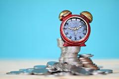 Миниатюрный стог часов и монеток на таблице стола Стоковая Фотография