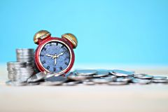 Миниатюрный стог часов и монеток на таблице стола Стоковые Изображения