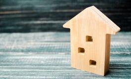 Миниатюрный трёхэтажный деревянный дом на голубой предпосылке minimalism Ипотека, кредит сбывание ренты домов квартир имущества р стоковое фото rf