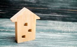 Миниатюрный трёхэтажный деревянный дом на голубой предпосылке minimalism Ипотека, кредит сбывание ренты домов квартир имущества р стоковые изображения rf