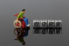 Миниатюрный человек масштабной модели в кресло-коляске с работой слова на шариках Стоковые Изображения