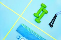 Минимализм, гантели, тапки, бутылка воды, веревочки скачки, полотенца, деталей спорт стоковые фотографии rf