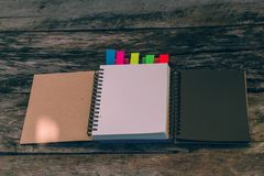 Минимальное место для работы: пустая тетрадь с цветами замечает плату на старом w Стоковые Изображения RF