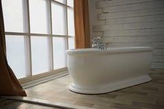Минималистский интерьер ванной комнаты Ванна в середине светлой комнаты на окне стоковое изображение rf