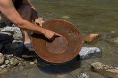 Минирование золотого самородка от реки Стоковые Фото