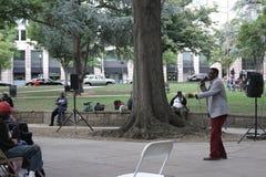 Министр церков проповедуя к бездомным людям и женщины в городе паркуют Стоковая Фотография
